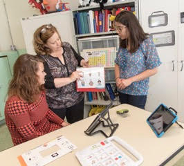 Pat Politano showing a communication book with pictures to two individuals by a table with communication aids (Project ATLiS; Photo: Robert Dupuis-Devlin)