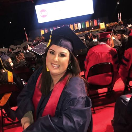 a graduate smiling in her cap and gown at commencement