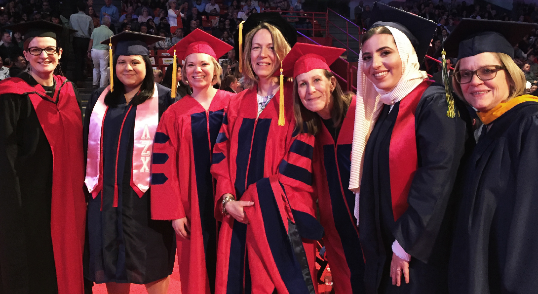 A group of faculty and graduates in their cap and gowns together at commencement