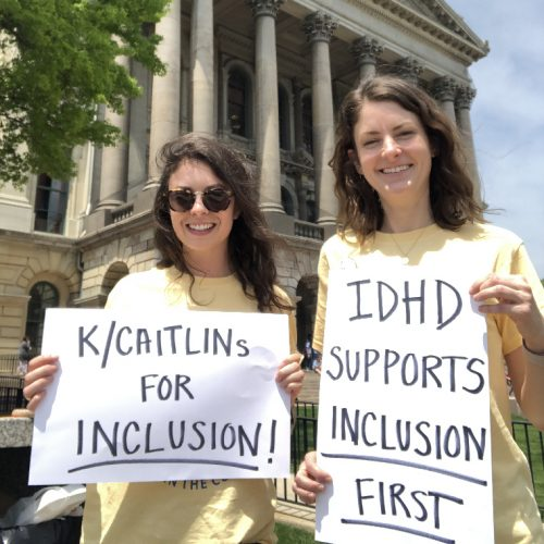 """Caitlin and Kaitlin of IDHD holding posters in support of inclusion: """"K/Caitlins for inclusion"""" and """"IDHD supports inclusion"""" in front of the Illinois State Capitol building"""