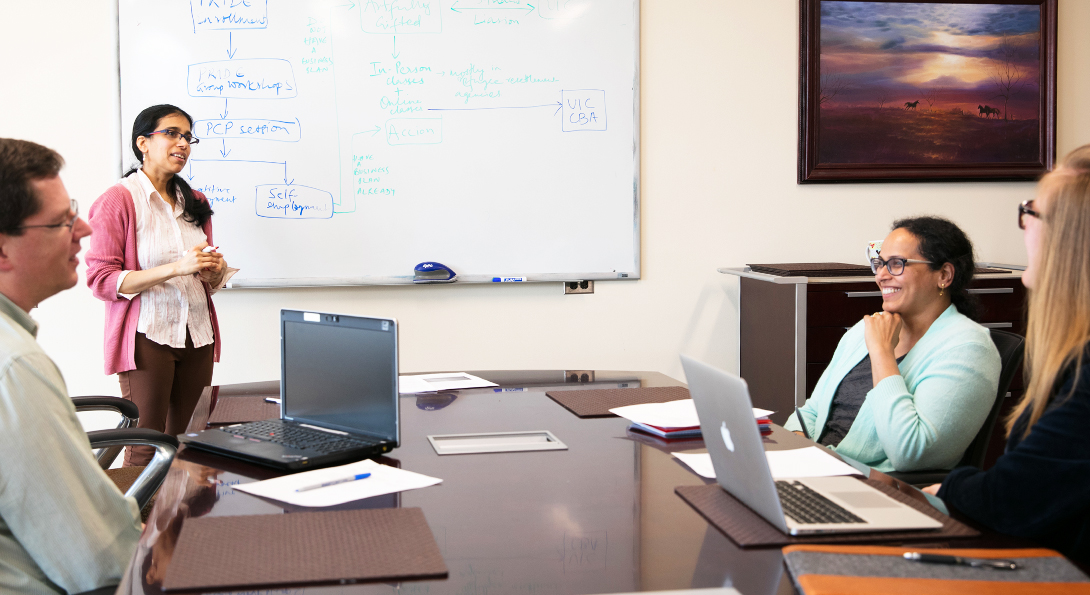 A researcher standing with a whiteboard with writing behind her and 3 individuals at a table in front of her with laptops, papers and pens