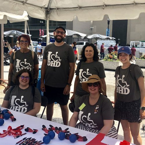 Faculty, staff and students together smiling at our information booth table at the disability pride parade